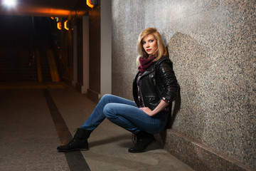 Young fashion woman in leather jacket sitting at the wall