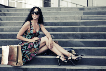 Young fashion woman with shopping bags sitting on the mall steps
