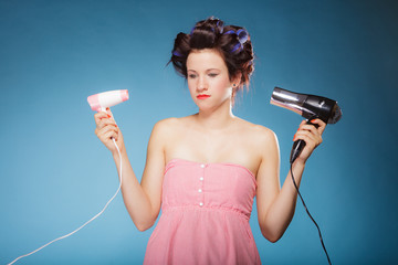 girl with curlers in hair holds hairdreyers