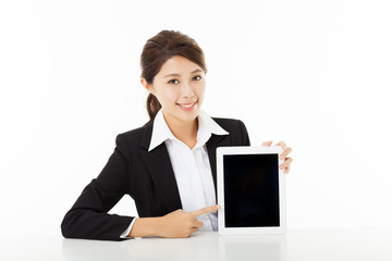 smiling young businesswoman  showing and pointing to the tablet