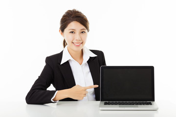 smiling young business woman  showing and pointing to the laptop