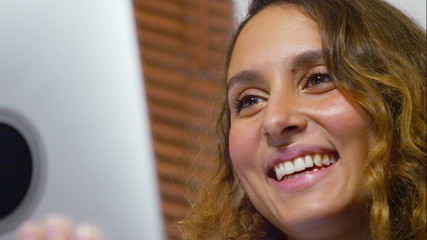 Attractive happy woman having a video call on a tablet