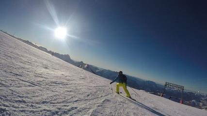 Alpine skier skiing short swings on ski slope