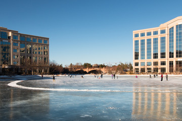 Ice skating rink on a frozen lake between office buildings