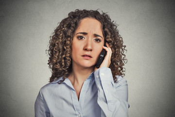 Sad young woman talking on mobile phone grey background