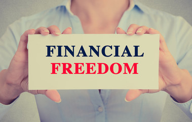Businesswoman hands holding card sign Financial freedom message