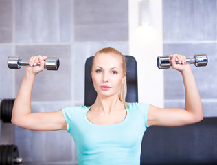 Attractive blond sporty girl doing shoulders training