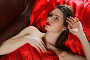 The girl in a red fabric lies on a sofa