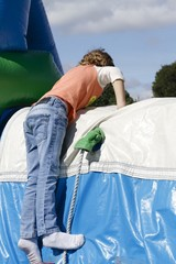 Boy climbing an inflatable slide