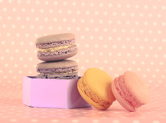 Tasty macaroons on pink polka dot background