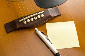 blank paper with pen on old acoustic guitar