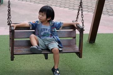 asian boy tried on swing. boy play swing in playground