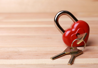 Heart-shaped padlock with key on wooden background