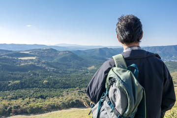 ザックを肩にかけて山を望む男性