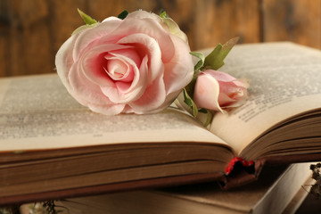 Books with flowers on wooden background