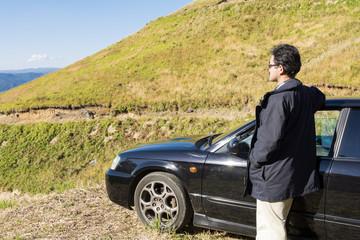 丘と車と男性