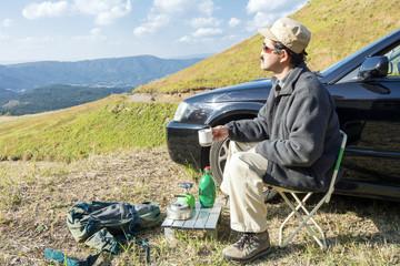 キャンプ用品と男性と車