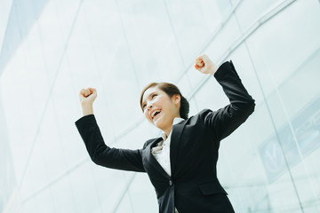 Young asian businesswoman rise her arms up