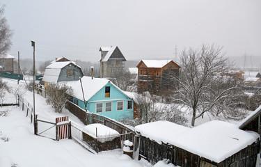 Летние дома на садовых участках зимним днем в снегопад