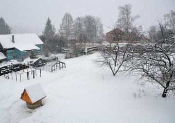 Заснеженный двор в деревне зимним днем в снегопад
