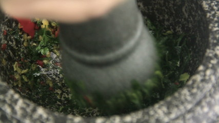 Pounding fresh herbs in a mortar with a pestle.