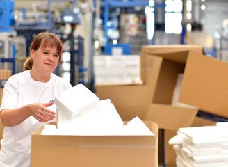 Arbeiterin verpackt Waren/ Styropor in Fabrik