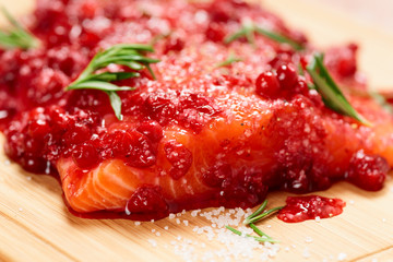 Salmon steak marinated in salt with rosemary and redberries