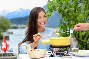 People eating Swiss cheese fondue having dinner