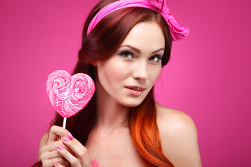 beautiful  merry redheaded girl with a large candy