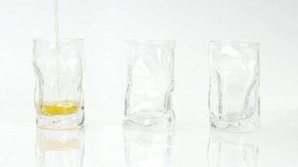 Strong liquor drink poured in three small glasses on white
