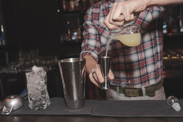Bartender is making cocktail, toned image