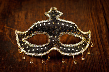 Glittering carnival mask on wooden table
