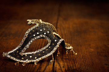 Black and golden mask on rustic table