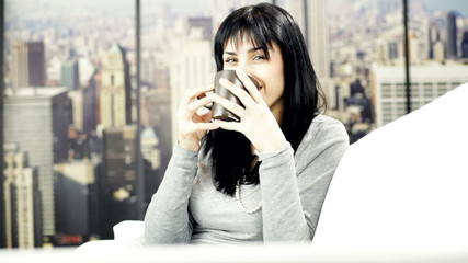 Young woman smiling looking camera while drinking coffee at home
