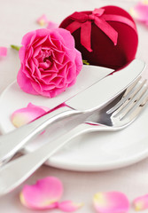 Romantic table setting with pink roses on a linen napkin