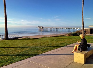 Woman working outdoors with laptop ocean view, La Jolla, CA