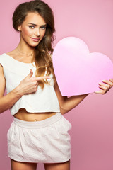 Glamourous woman with pink heart in hand. Love sign