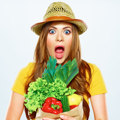 woman with green vegan food. paper bag. surprise emotion.