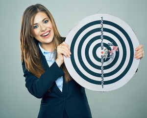 Business woman smiling and holding big target of darts.