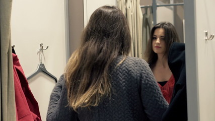 Young woman trying jacket in fitting room at shop