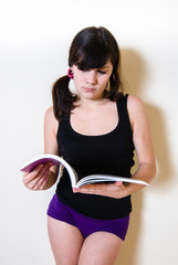 Young pretty brunette in short standing and reading a book