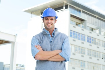 Male architect standing arms crossed outside building