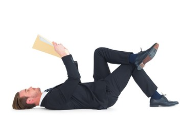 Relaxed businessman lying and reading document