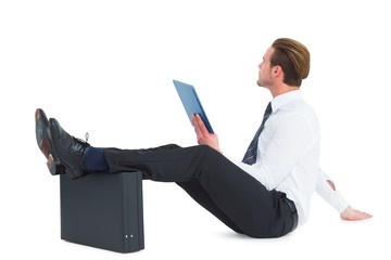 Businessman using tablet with feet up on briefcase