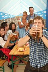 Mann in Tracht trinkt Bier