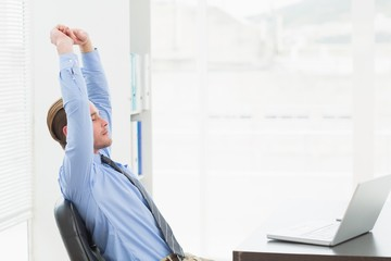 Focused businessman stretching at his desk