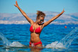 Beautiful young woman in bikini on the beach splashing water