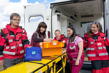 Group paramedics with medicine chest on ambulance background
