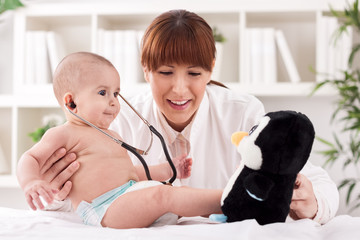 Funny baby playing with doctor