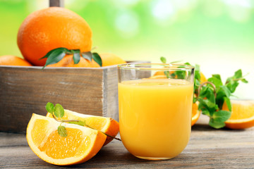 Glass of orange juice with crate of oranges and slices